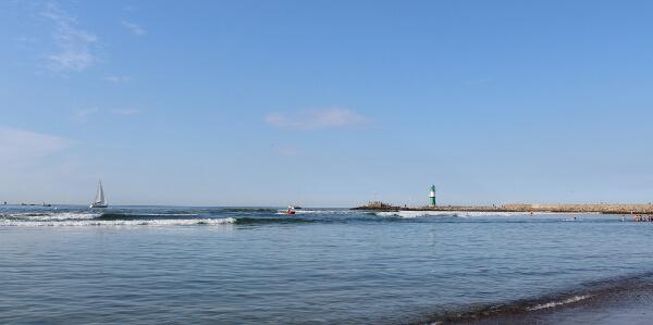 Blick vom Strand aus auf den grünen Leuchtturm in Warnemünde