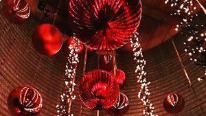 Rote Weihnachtsbaummkugel von der Decke hängend mit Lichterketten