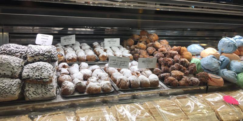 Bäckerei-Auslage mit verschiedenen Backwaren, unter anderem mit Fritelle veneziana
