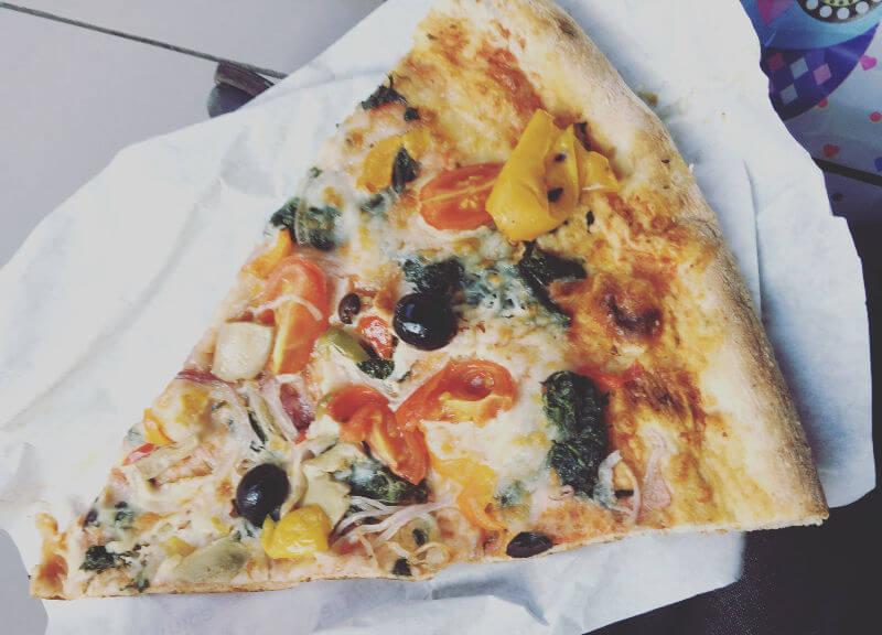 Pizza-Stück mit Oliven, Paprika und Tomaten auf weißem Pappteller