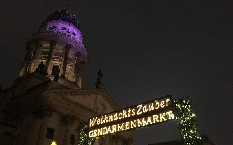 """Eingang Weihnachtsmarkt am Gendarmenmarkt mit beleuchtetem Schriftzug """"Weihnachtszauber Gendarmenmarkt"""", violett beleuchteter Dom"""