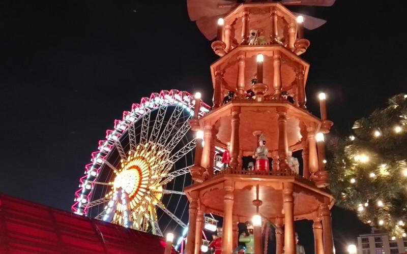 Weihnachtspyramide und Riesenrad bei Nacht und beleuchtet auf dem Weihnachtsmarkt am Roten Rathaus in Berlin
