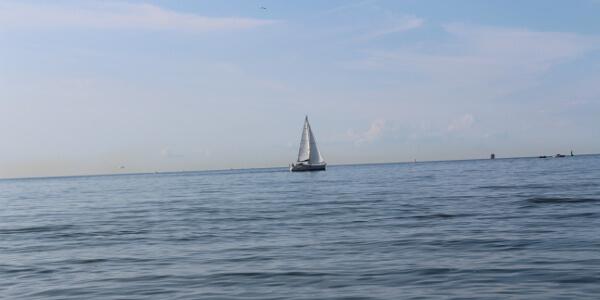 Blick vom Strand auf ein Segelboot auf der Ostsee als Zeichen für Ruhe