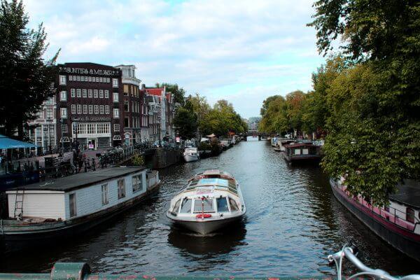 Amsterdam: Blick von Brücke auf Grachte, vorbeifahrendes Boot