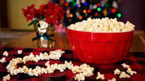 Schale mit Popcorn auf Tisch mit verstreutem Popcorn vor geschmücktem Weihnachtsbaum