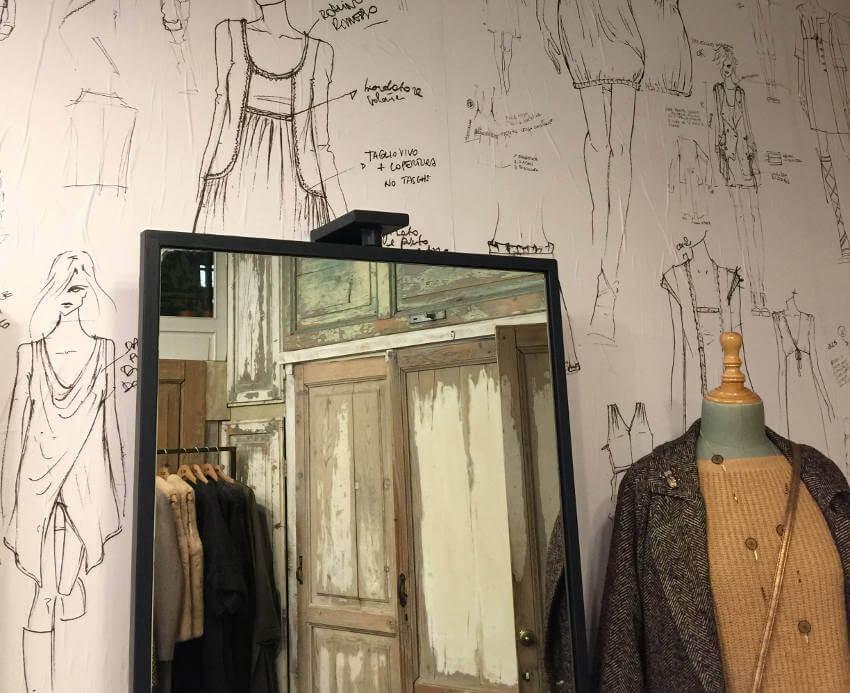 Shop mit Modezeichungen als Tapete, Spiegel und Schneiderpuppe