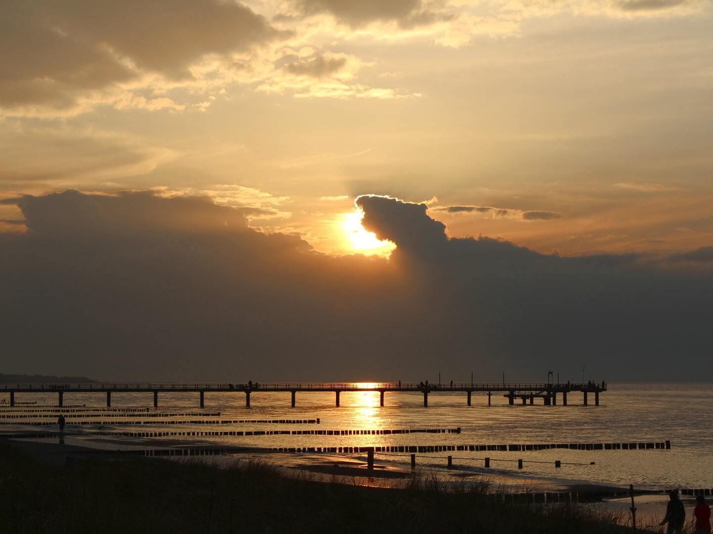 Blick von Strandpromenade auf das Meer und Seebrücke bei Sonnenuntergang