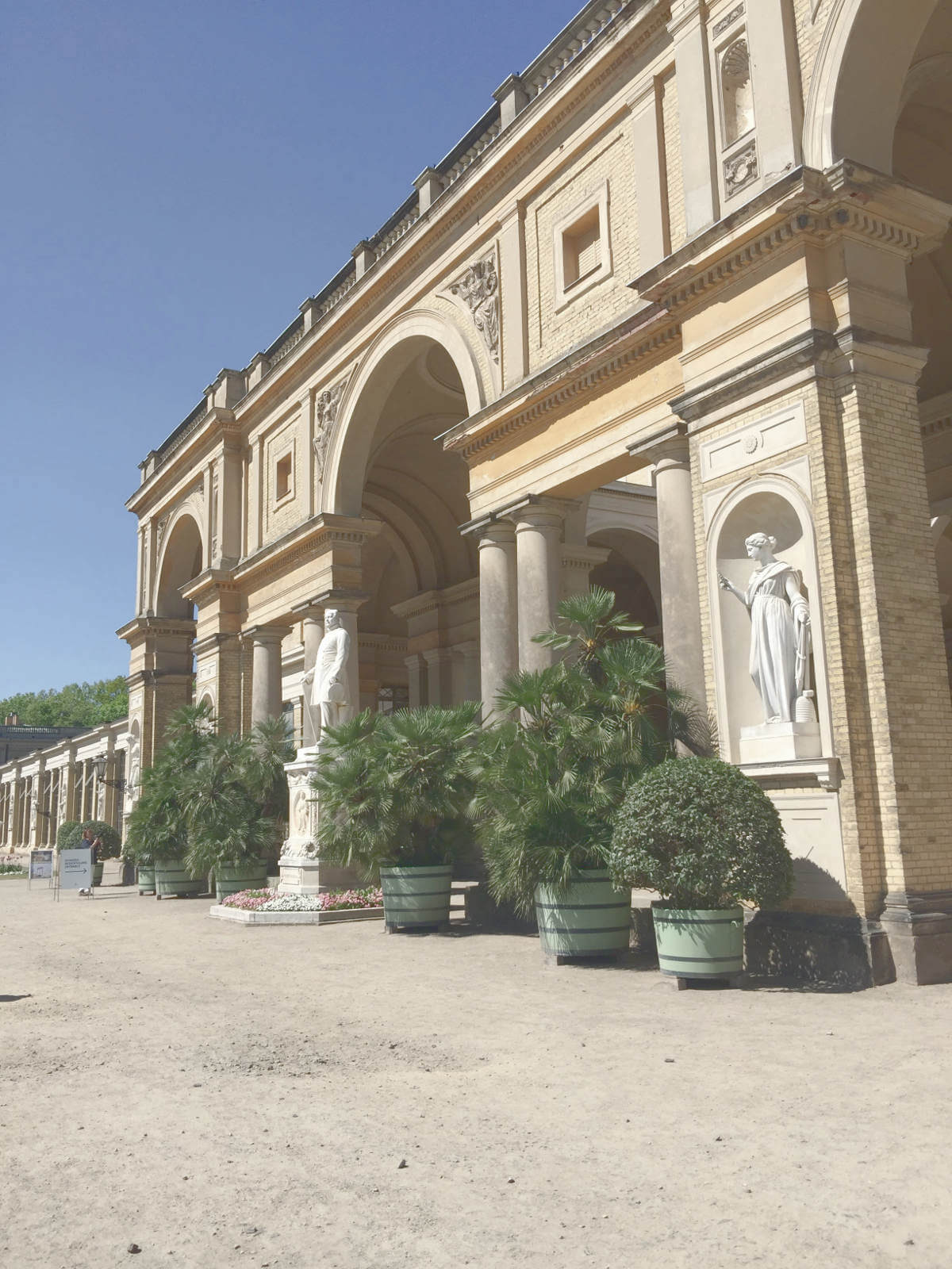Blick auf Hauptgebäude des Orangerieschloss mit Pflanzen am Eingang im Park Sanssouci in Potsdam, Brandenburg