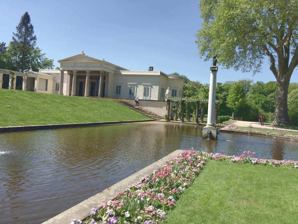 Blick auf Schloss Charlottenhof mit Teich, Säule und Blumenbeeten im Park Sanssouci in Potsdam, Brandenburg