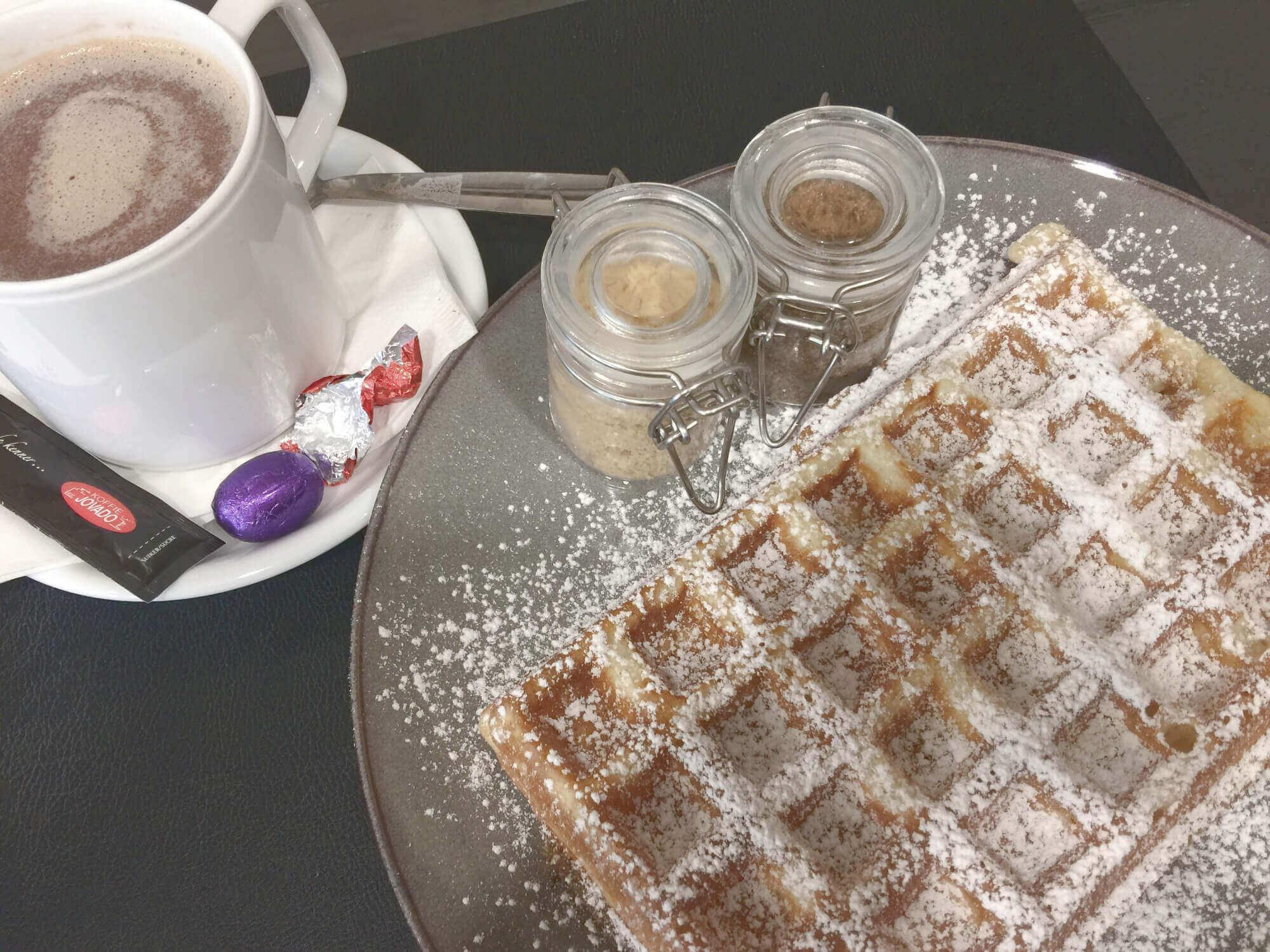 Waffel nach Brüssler art mit verschiedenen Zuckersorten und heiße Schokolade im Café Balthasar in Brügge, Belgien
