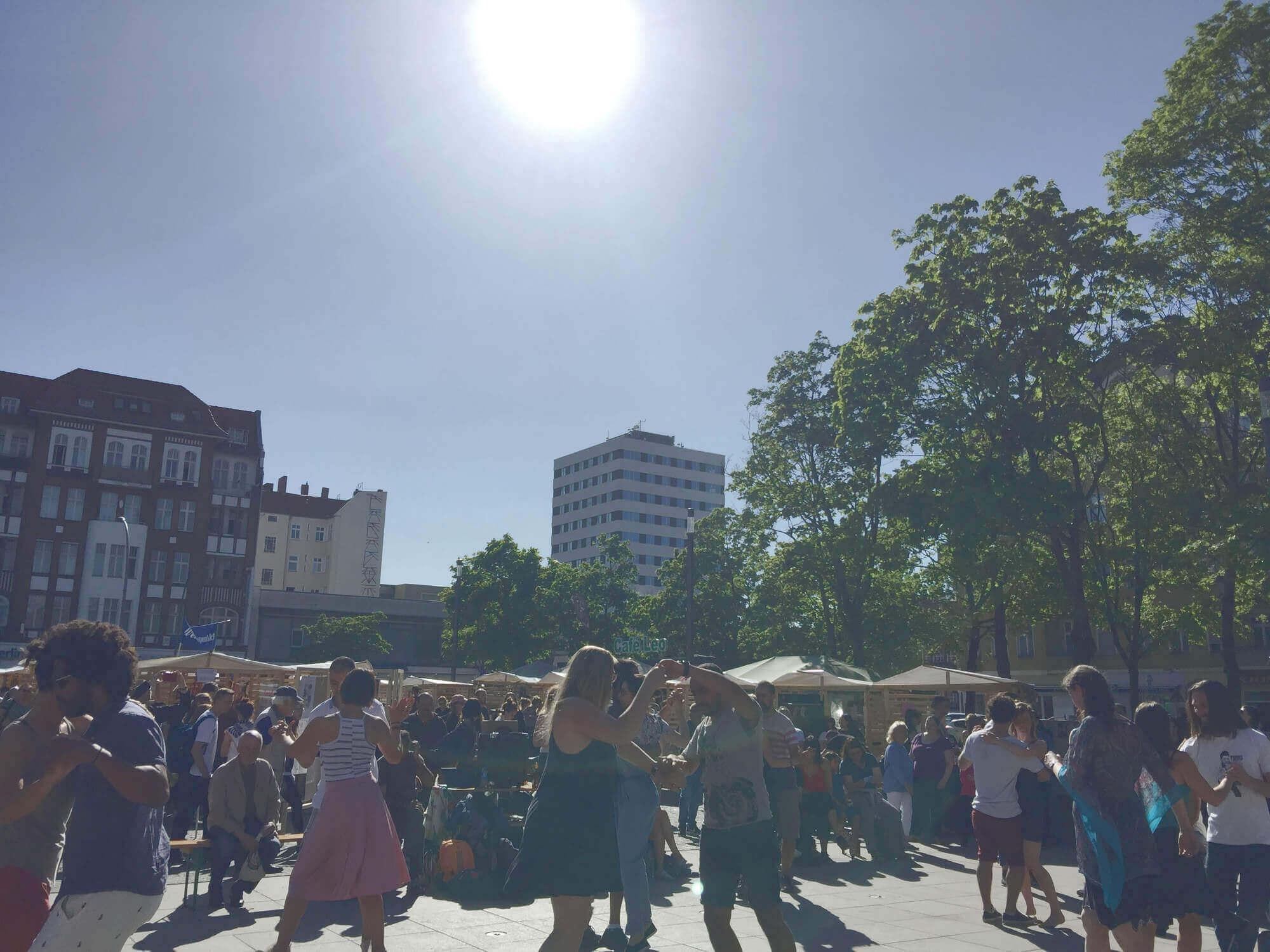 Tanzende Menschen auf Markt in Sonnenschein