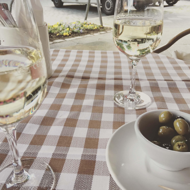 Tisch mit karierter Tischdecke 2 Weingläsern mit Weißwein und einer kleinen Schale mit grünen Oliven