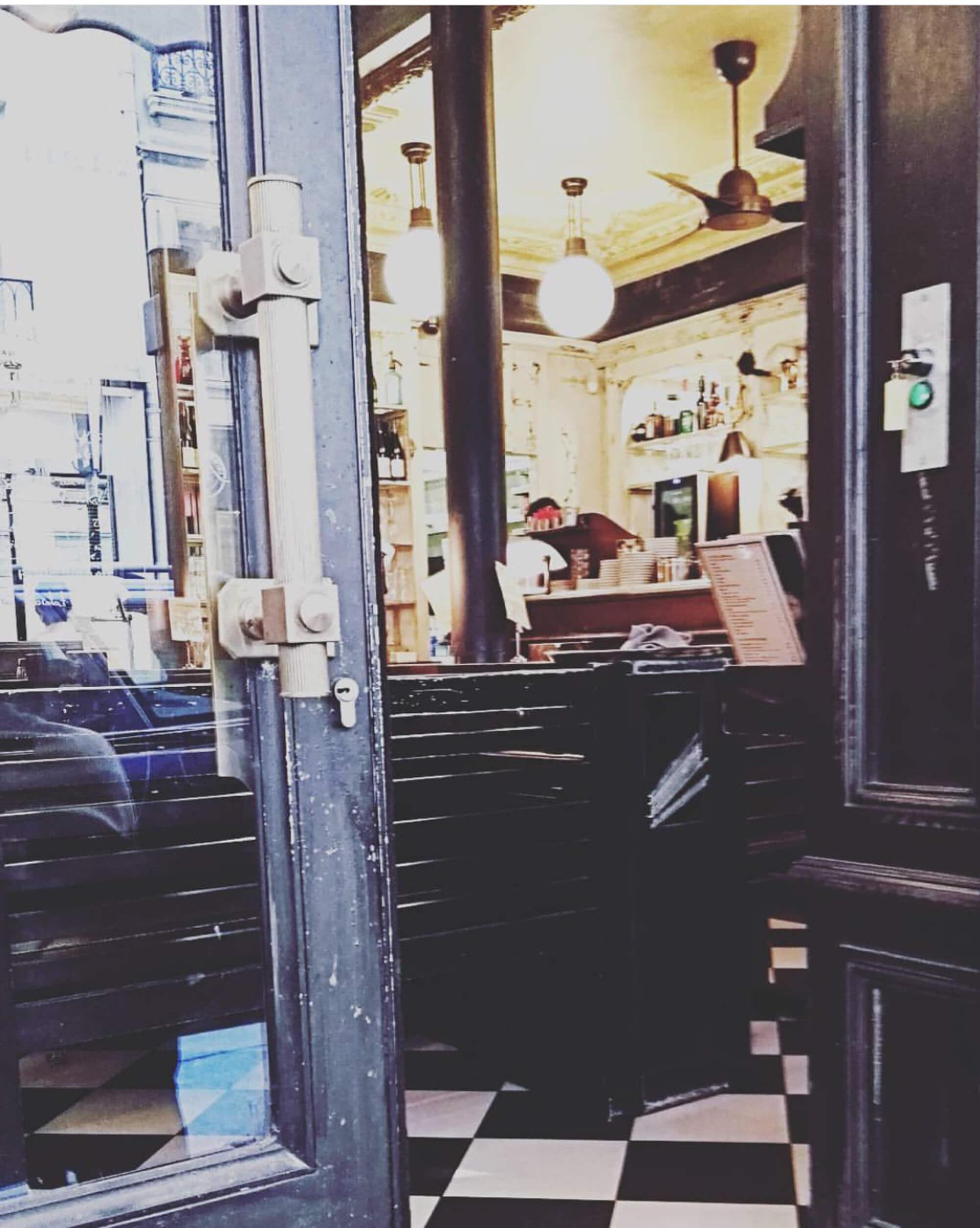 Blick auf und in Eingangstür eines Cafés in Paris.