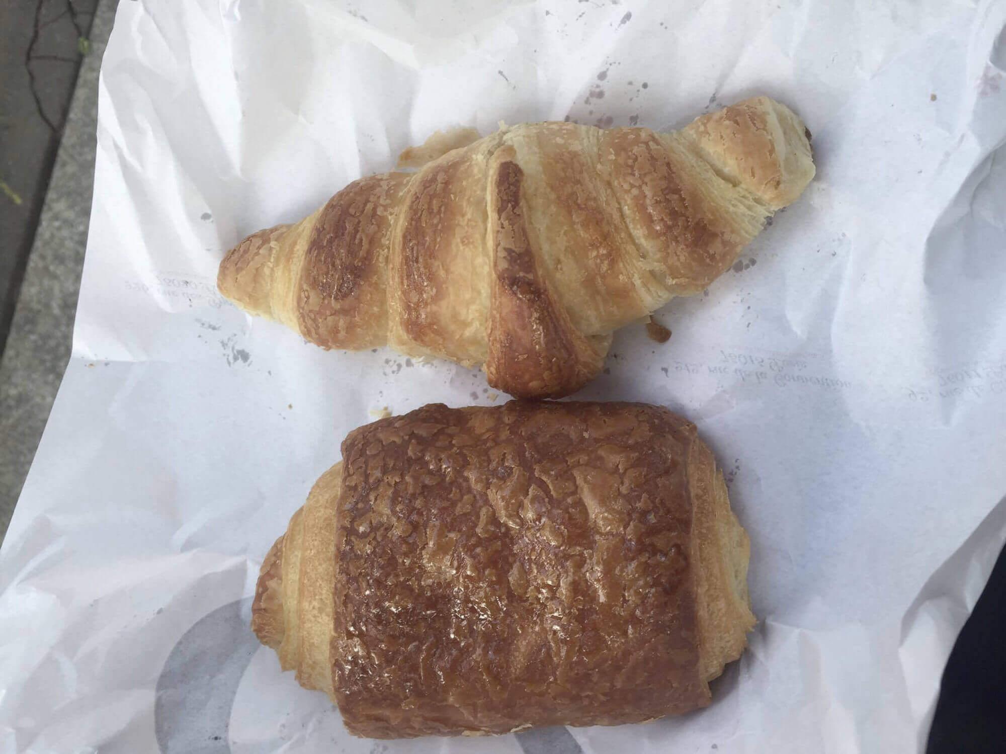 Croissant und Pain au Chocolate auf weißer Bäcker-Tüte