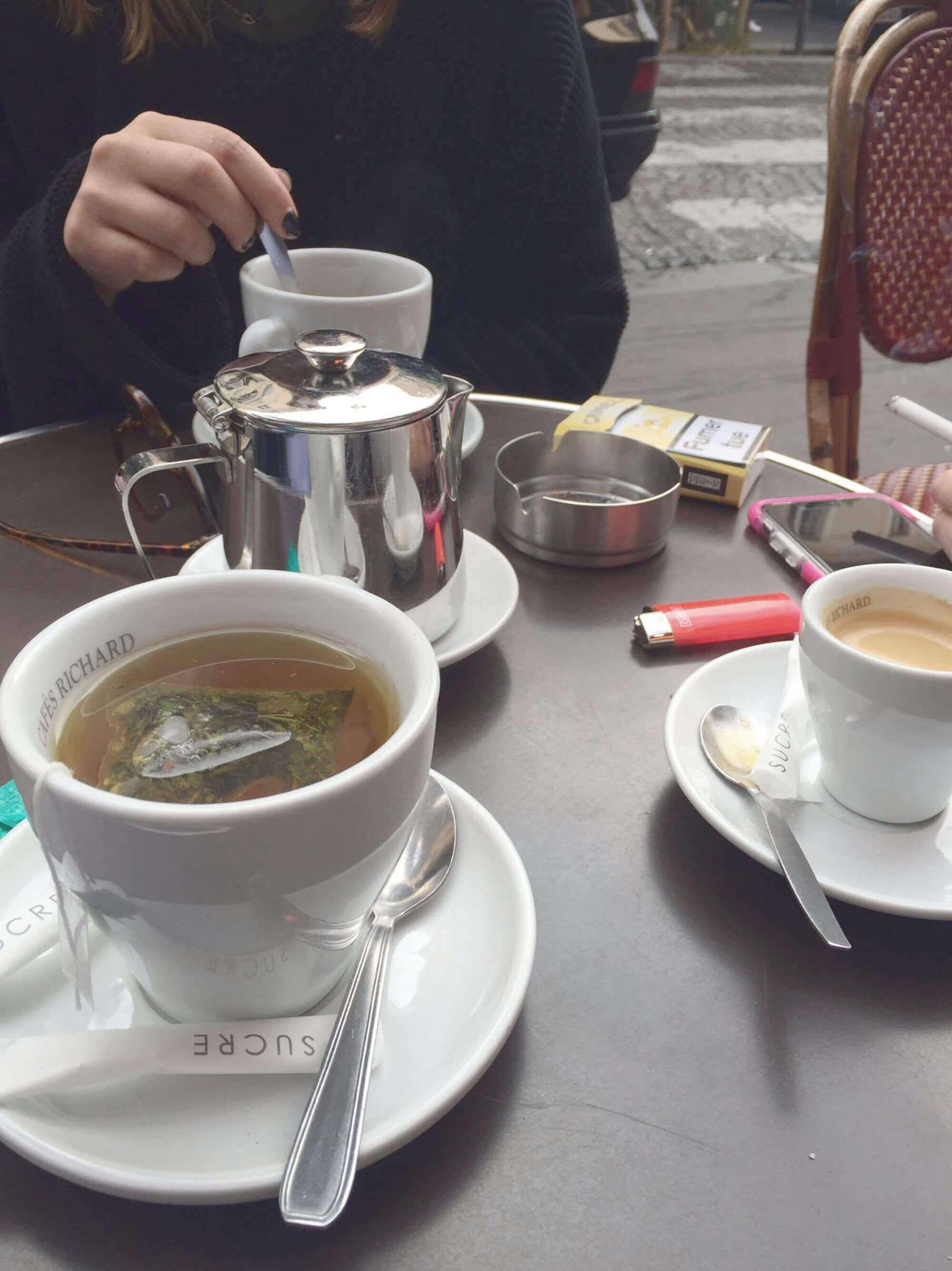 Tisch mit 2 Kaffe + 1 Tee, Miclhkännchen, Zigaretten und Feuerzeug