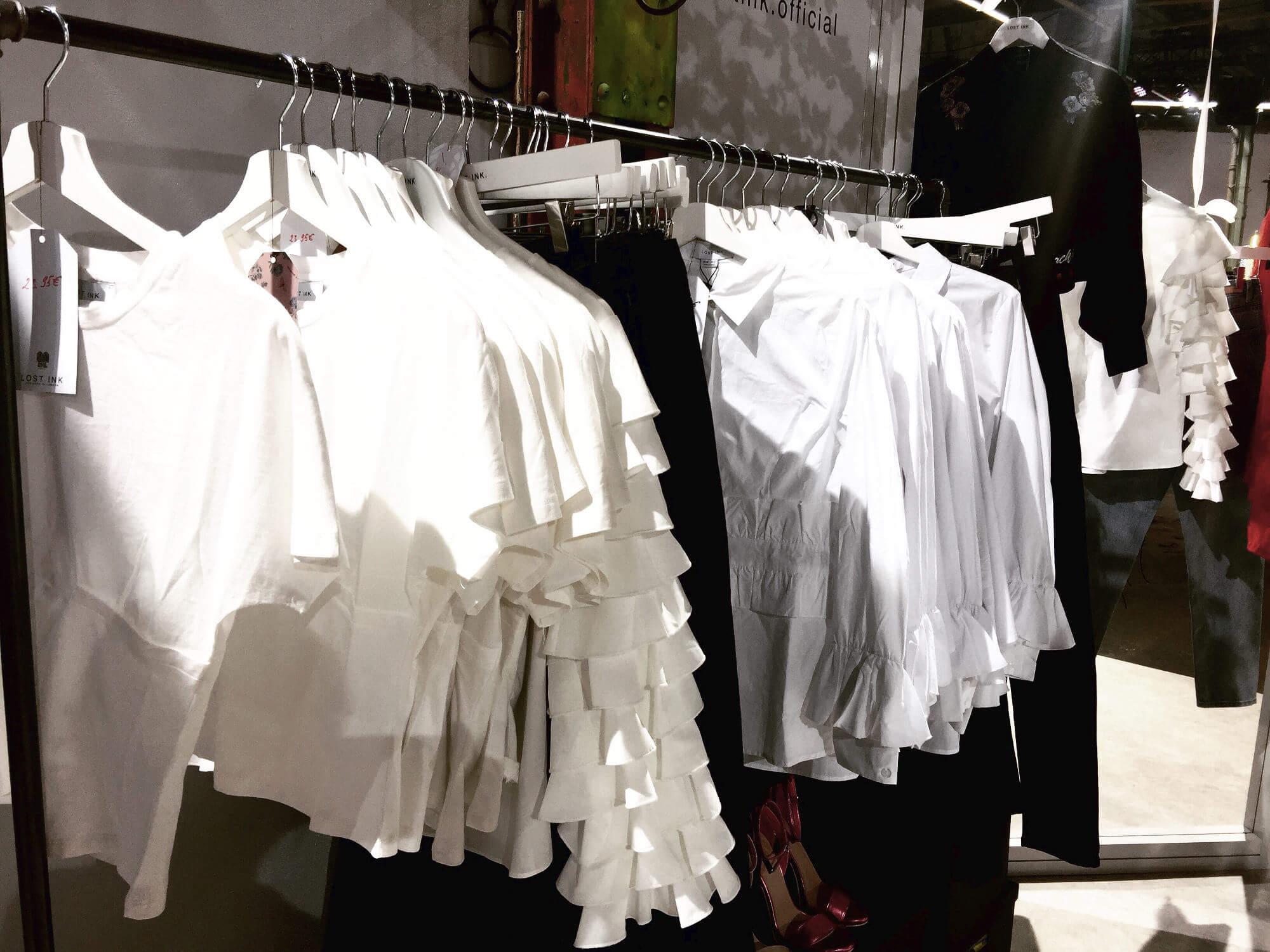 Kleiderstange mit weißen Blusen und schwarzen Hosen