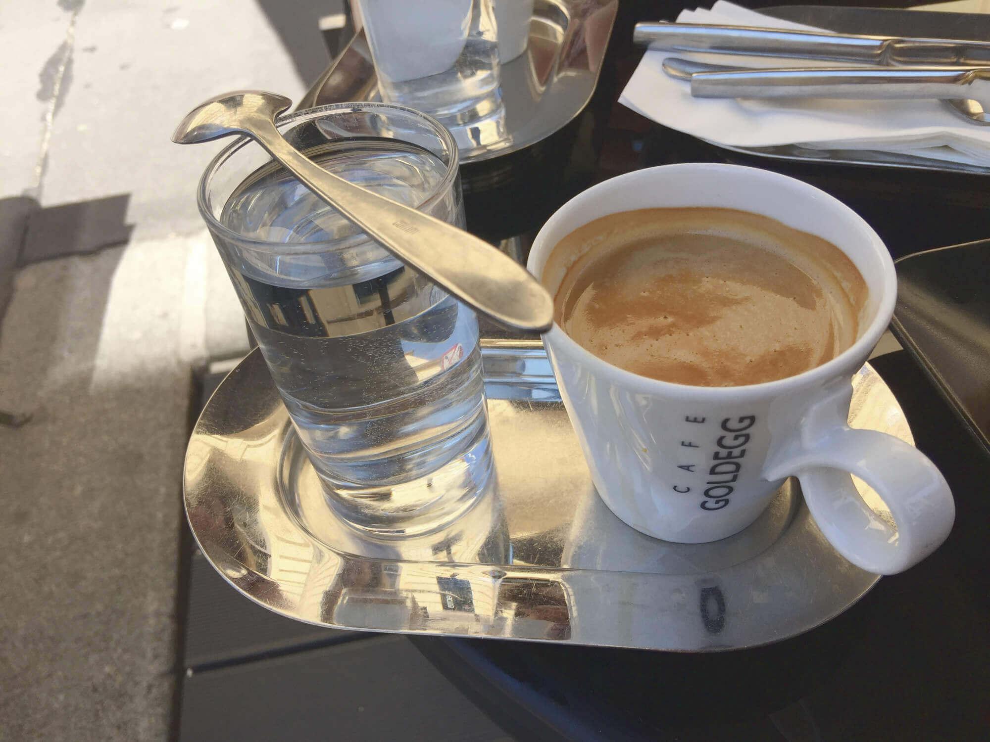 Kleiner Brauner mit Wasser auf Silbertablet in Kaffeehaus in Wien