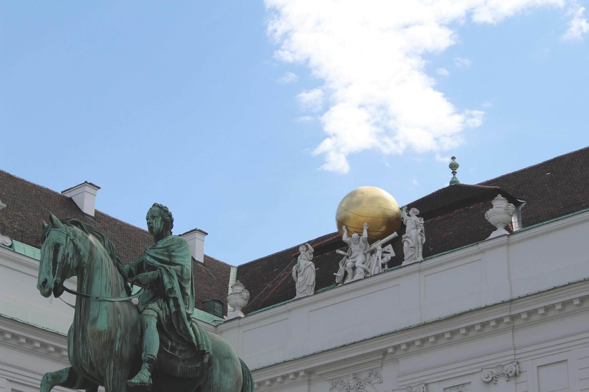 Blick auf Statue und Weltkugel am Österreichischen Parlament in Wien