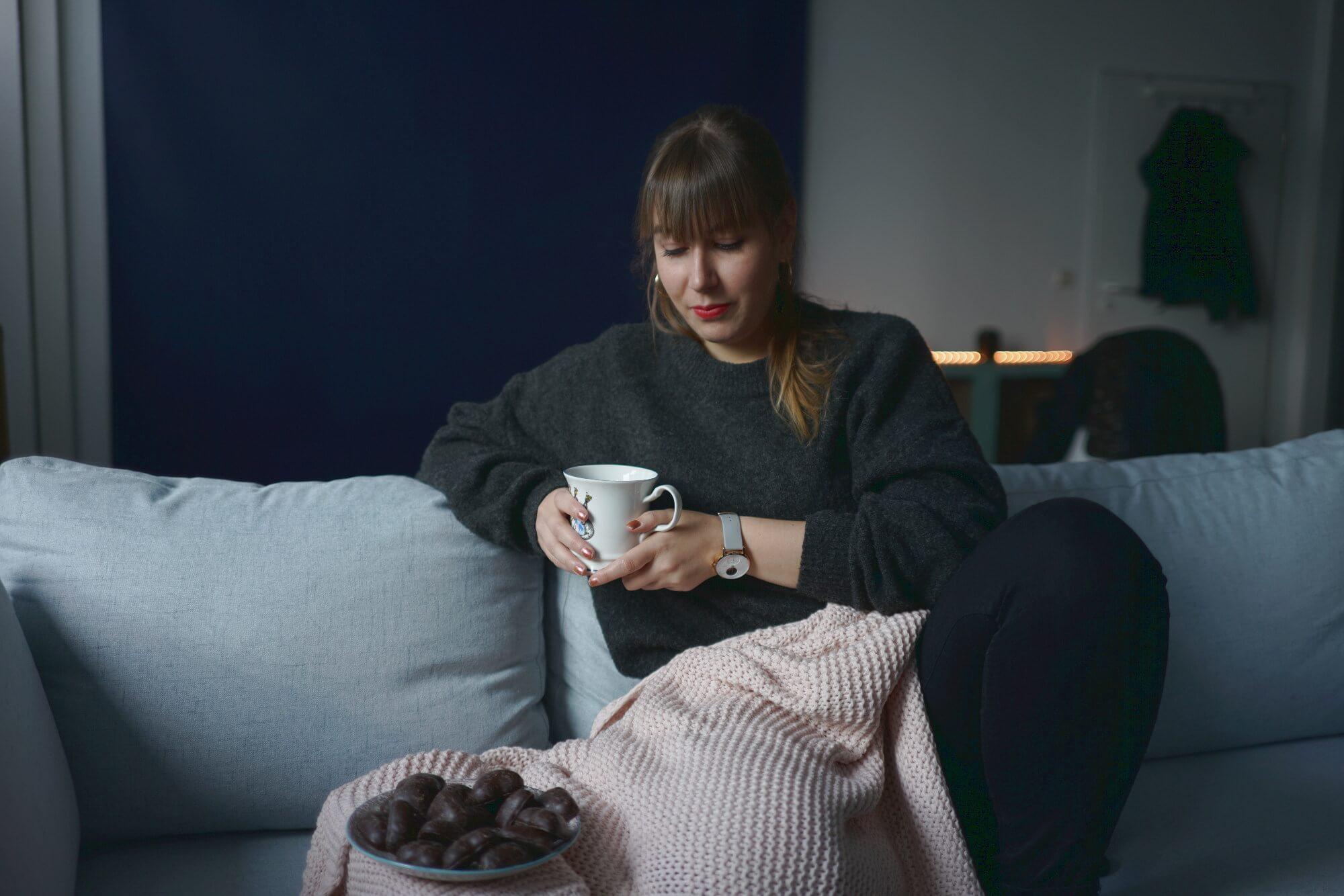 Frau auf Sofa mit Tee und Lebkuchen
