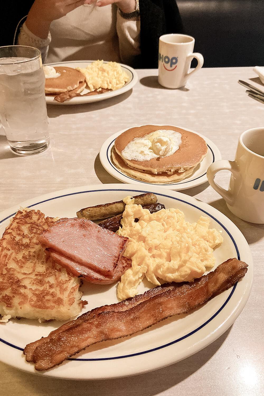 Amerikanisches Frühstück mit Hashbrownies, Schinken, Bacon, Würstchen, Rührei und Pancakes bei IHOP
