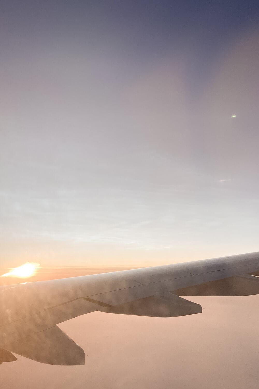 Blick aus Flugzeug auf aufgehende Sonne