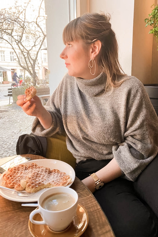 Frau beim Waffeln essen in der Ostfee in Berlin-Prenzlauer Berg