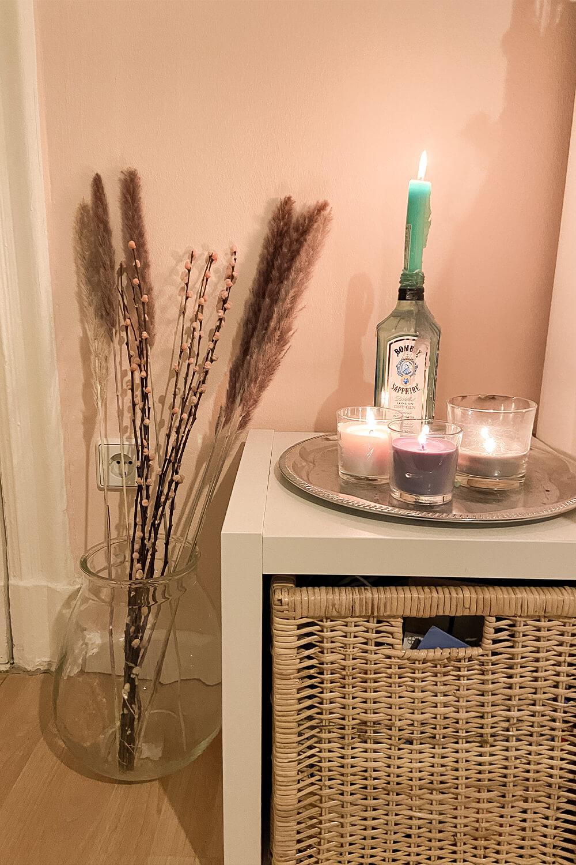 Interior: Brennende Kerzen auf Kleinkommode neben Bodenvase mit Trockenblumen