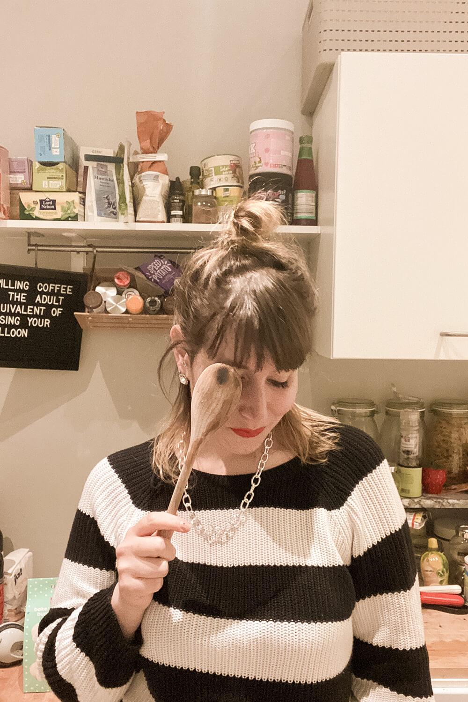 Frau in Küche mit Kochlöffel in der Hand