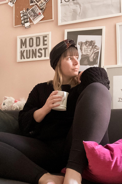 Frau mit Kaffee am Sofa